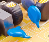 Electronic capacitor mounted on board with other components — Stock Photo