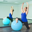 Young woman exercising with a ball in front of a large mirror - Stock Photo