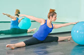 Young woman exercising with a ball in front of a large mirror — Stock Photo
