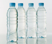 Bottles of mineral water on white base with bright background — Stock Photo