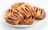 Group flaky pastries filled with jam on white plate — Stock Photo