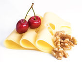 Leerdammer cheese slices with nuts and cherries on white base — Stock Photo