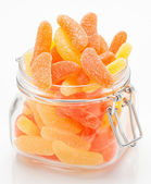 Sugary gummy orange and lemon in glass jar — Stock Photo