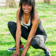 Foto Stock: Black girl prepares for sports in public park