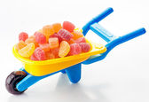Toy wheelbarrow full of sugary jellies — Stock Photo