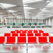 Several rows of empty red seats in the hall of a great station — Stock Photo