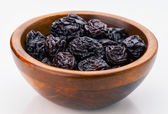 Prunes group in wooden bowl — Stock Photo