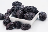 Group of prunes in small porcelain tray — Stockfoto