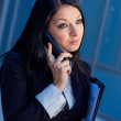 Executive woman talking on phone in an office building — ストック写真