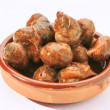 Escargot cooked in sauce served in earthenware dish — Stock Photo