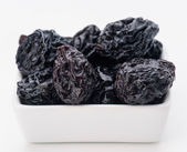 Group of prunes in small porcelain tray — Stock Photo