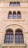 Wooden windows in a building wall stone in Europe — Stockfoto