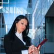 Stock Photo: Executive with red folder in front of office building