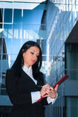 Executive with red folder in front of an office building — Foto de Stock