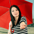 Young girl checks if it rains with a red umbrella, isolated on w — Stock Photo