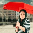 Young girl protects the storm with he red umbrella — Stock Photo