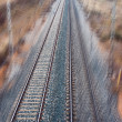 Stock Photo: Modern railway track across field towards city