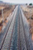 Modern railway track across the field towards the city — Foto Stock