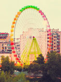 Fair Ferris wheel adorned with lights spinning at dusk — 图库照片