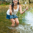 Cheerful girl splashing water playing in the river — Stock Photo