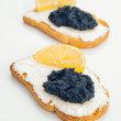 Black caviar on toasted bread with cheese and lemon — Stock Photo
