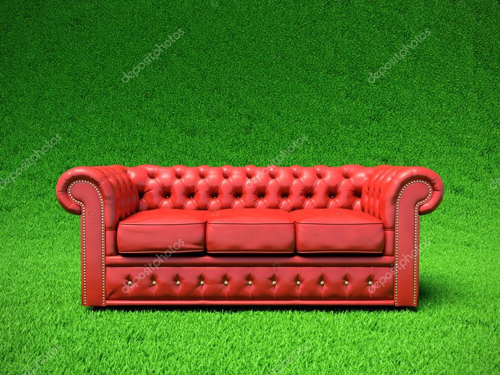 Red classic leather sofa on green field — Stock Photo #12569450