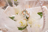 Wedding rings on a white flowers — Stock Photo