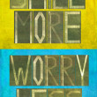 "Earthy background image and design element depicting the words ""Smile more, worry less"" - Stock Photo"