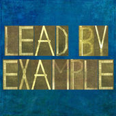 "Earthy background image and design element depicting the words ""Lead by example"" — Stock Photo"