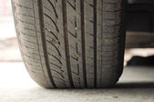 Close up of a car tire on a dirty road. — Stock Photo