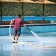 Man washing swimming pool — Stock Photo