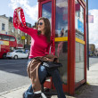 Young woman waving with london red phone booth at back — Stock Photo