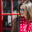 Fashionable young womleaning on red phone booth — Stock Photo #14059473
