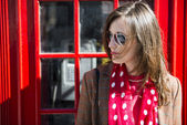 Fashionable young woman leaning on red phone booth — Stock Photo