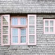 Beautiful pink windows on the facade of a wooden House — Stock Photo
