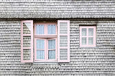 Beautiful pink windows on the facade of a wooden House — Stockfoto