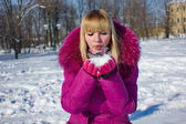 Girl blowing on snow — Stock Photo