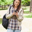 Stock Photo: Young smiling student using smartphone