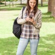 Stock Photo: Young student standing while using smartphone