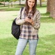 Stock Photo: Young student posing while using smartphone