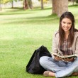 Stock Photo: Smiling teenager sitting while holding textbook