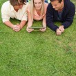 Three young using a tactile tablet — Stock Photo