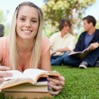 Smiling girl lying in front of her books in a park — Stock Photo