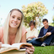 Portrait of a girl lying while reading books in a park — Stock Photo
