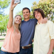 Stock Photo: Three smiling friends taking pictures of themselves