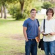 Portrait of two standing male students talking - Stock Photo