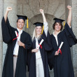 Happy graduates raising arm — Stock Photo