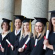 Smiling graduates posing in single line — Stock Photo #13908151