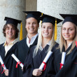 Portrait of smiling graduates posing in single line — Stock Photo