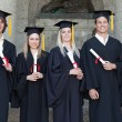 Stock Photo: Smiling graduates posing